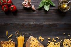 Droge gemengde deegwaren en groenten op de donkere houten mening van de lijstbovenkant, met exemplaarruimte Stock Afbeeldingen