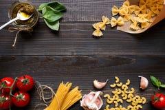 Droge gemengde deegwaren en groenten op de donkere houten mening van de lijstbovenkant, met exemplaarruimte Royalty-vrije Stock Afbeeldingen