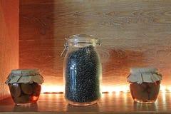 Droge korrels in duidelijke glaskruiken op een plank met verlichting stock afbeelding
