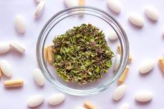 Droge kruiden in een kom op de voedingsachtergrond van supplementenpillen Alternatieve kruidengeneeskunde, naturopathy en homeopa stock afbeeldingen