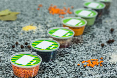 Droge kruiden in plastic containers op een marmeren achtergrond Stock Afbeeldingen