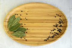 Droge laurierboombladeren, zwarte peperbollen stock foto