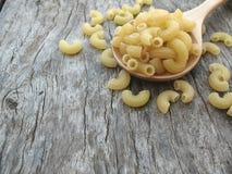 Droge macaroni en woodeb lepel met oude houten textuur Stock Fotografie