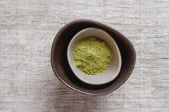 Droge Matcha-thee in een kleine bruine plaat Grijze houten achtergrond bovenkant Royalty-vrije Stock Fotografie