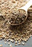 Droge organische dillezaden in een houten lepel op een zwarte achtergrond verticaal royalty-vrije stock afbeelding