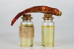 Droge peper en een flesje olie op een witte keukenlijst Kruiden royalty-vrije stock afbeeldingen