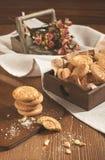 Droge rozen en ronde koekjes op houten plank Stock Afbeelding