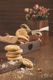 Droge rozen en ronde koekjes op houten plank Stock Foto's