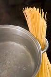 Droge spaghetti met kokend water in een pan stock foto