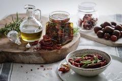 Droge tomaten in een kruik met verse kruiden en olijfolie Royalty-vrije Stock Foto