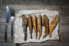 Droge vissen met vork en mes op de lijst Zoute droge rivier fis Stock Foto