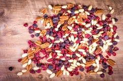 Droge vruchten - pecannoot, Amerikaanse veenbes, rozijn, amandel op houten royalty-vrije stock afbeelding