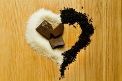Droge zwarte thee en suiker in de vorm van een hart Stock Foto