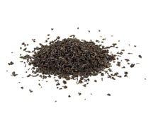 Droge zwarte theebladen op wit Stock Foto's