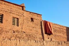 Drogend tapijt op de aarden muren van het huis stock afbeelding
