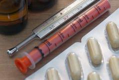 Droger, apotekpills, injektionsspruta och termometer Arkivbilder