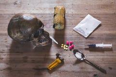 Droger av olika slag och mänskliga skallar på trätabellen, sänka arkivfoton