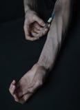 Droghe della siringa della persona dedita delle mani Immagini Stock Libere da Diritti