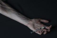 Droghe della siringa della persona dedita delle mani Fotografia Stock