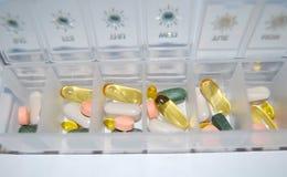 Droghe delle pillole colorate macro in contenitore Fotografie Stock