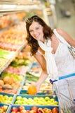 Drogheria - l'acquisto della donna sceglie la frutta Fotografia Stock