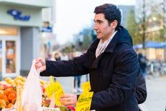 Drogherie d'acquisto dell'uomo sul supporto del mercato degli agricoltori Fotografia Stock Libera da Diritti