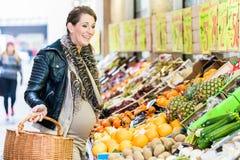 Drogherie di acquisto della donna incinta sul mercato degli agricoltori Fotografie Stock Libere da Diritti
