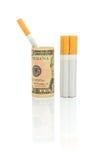 Palenie zabronione. Papierosy i pieniądze na białym tle. Zdjęcia Stock
