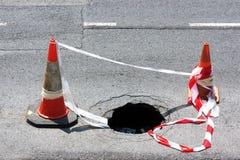 Drogowa dziura z ostrzeżenie rożkami Zdjęcie Royalty Free