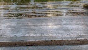 Drogowa podeszczowa woda opuszcza tło z niebieskiego nieba odbiciem i okręgi na zmroku asfalcie prognoza Obraz Royalty Free