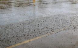 Drogowa podeszczowa woda opuszcza tło z niebieskiego nieba odbiciem i okręgi na zmroku asfalcie prognoza Obrazy Royalty Free