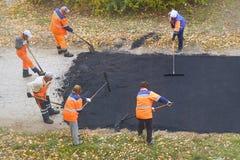Drogowe uliczne naprawianie pracy Pracownicy budowlani podczas asfaltować drogę zdjęcie stock