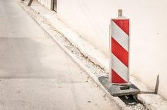 Drogowego ruchu drogowego znaka praca z czerwonymi i białymi barierami na ulicznej budowie w mieście naprzód Zdjęcia Royalty Free