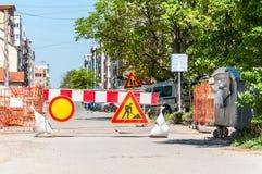 Drogowego ruchu drogowego znaka praca z czerwonymi i białymi ostrzegawczymi barierami na ulicznej budowie w mieście naprzód Zdjęcia Royalty Free
