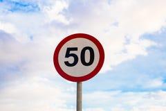 Drogowego znaka prędkości ograniczenie 50, ruch drogowy podpisuje wewnątrz niebieskiego nieba tło Obraz Royalty Free