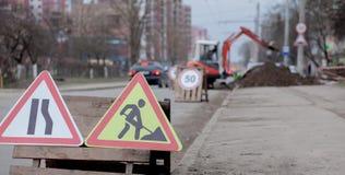 Drogowi znaki, objazd, drogi naprawa na ulicznej tła, ciężarówki i ekskawatoru głębienia dziurze, obraz stock