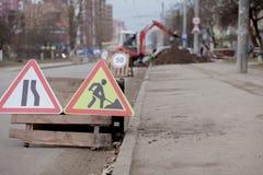 Drogowi znaki, objazd, drogi naprawa na ulicznej tła, ciężarówki i ekskawatoru głębienia dziurze, obrazy royalty free