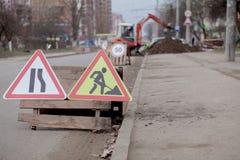 Drogowi znaki, objazd, drogi naprawa na ulicznej tła, ciężarówki i ekskawatoru głębienia dziurze, fotografia royalty free
