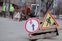 Drogowi znaki, objazd, drogi naprawa na ulicznej tła, ciężarówki i ekskawatoru głębienia dziurze, zdjęcia stock