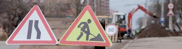 Drogowi znaki, objazd, drogi naprawa na ulicznej tła, ciężarówki i ekskawatoru głębienia dziurze, zdjęcie stock