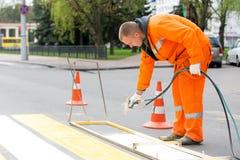 Drogowy pracownik zaznacza zwyczajnego skrzyżowanie linii Obraz Stock