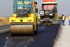 Drogowy rolownik zrównuje świeżego asfaltowego bruk na pasie startowym jako część Danube delty lotniska międzynarodowego planu ro Obraz Royalty Free