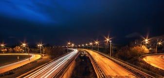 Drogowy ruch drogowy w mieście na mostach przy nocą, panoramiczny dramatyczny miasto krajobraz Fotografia Royalty Free