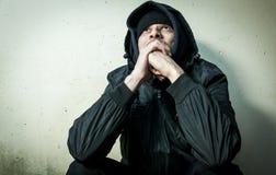 Drogue sans abri d'homme et intoxiqué d'alcool seul s'asseyant et déprimé sur la rue dans des vêtements d'hiver sentant froid et  images stock