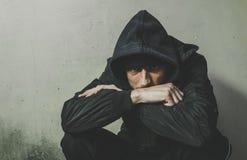 Drogue sans abri d'homme et intoxiqué d'alcool seul s'asseyant et déprimé sur la rue dans des vêtements d'hiver sentant froid et  image stock