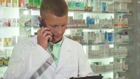 Droguero que contesta al teléfono mientras que usa la tableta almacen de video