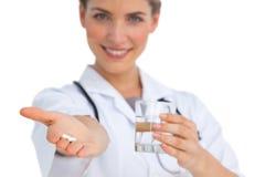 Drogues et verre d'eau tenu par l'infirmière Image stock