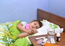 Drogues sur une table de chevet contre la petite fille malade se situant dans a image stock