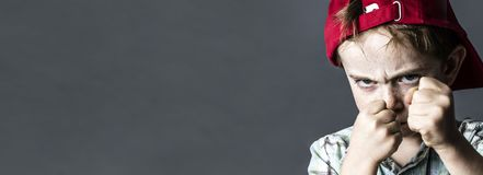Drohender Junge mit den Sommersprossen und rotem Hut, die, Fahne heftig schaut lizenzfreie stockfotografie
