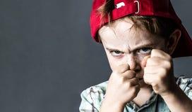Drohender Junge mit Sommersprossen und dem hinteren Schauen des roten Hutes heftig stockfotografie